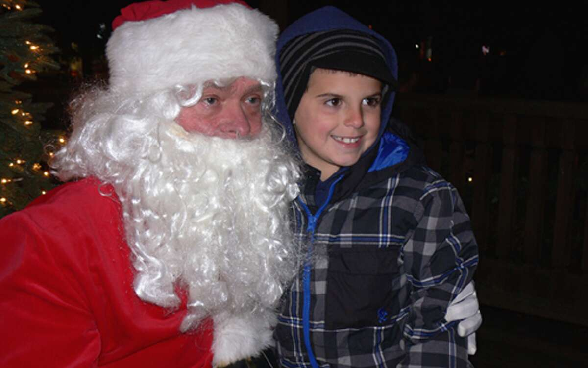 A youngster poses with Santa so a parent can take a photo during the Huntington Green event.