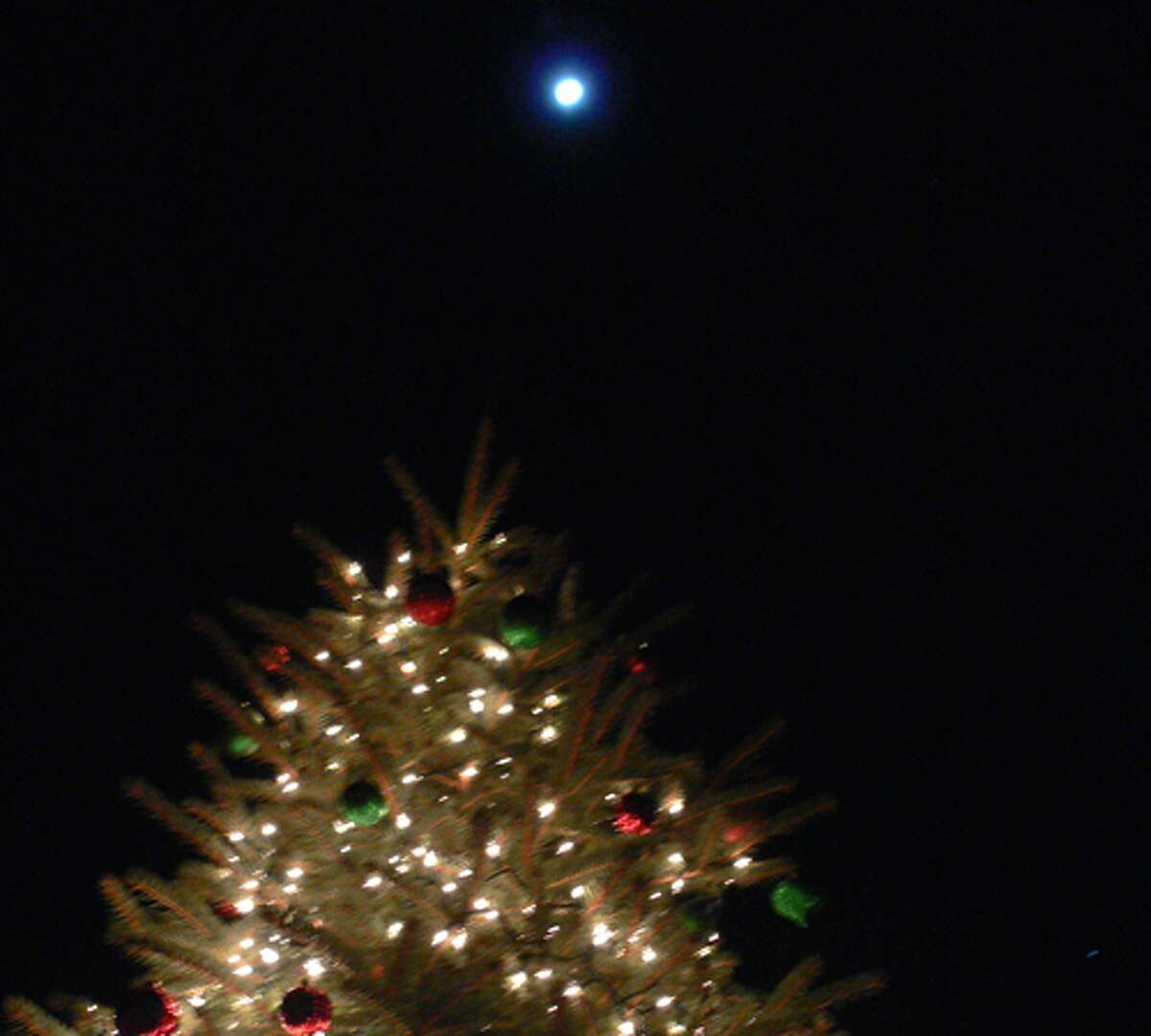 A view of the lit tree on late Sunday night, with a full moon visible above it in the sky.