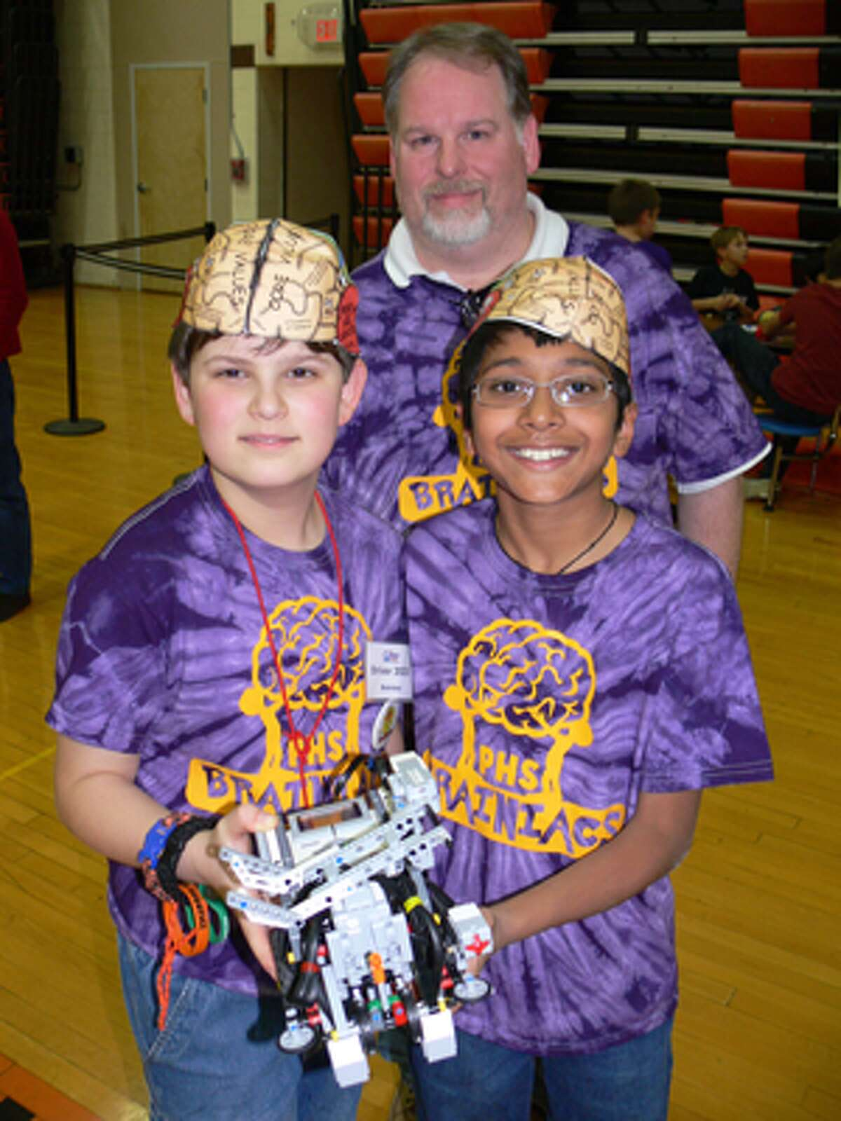 At last week's regional tournament, Evan Kryger, left, and Archit Bhargava, members of the Perry Hill Brainiacs, with coach Bob Kryger, who is Evan's father.