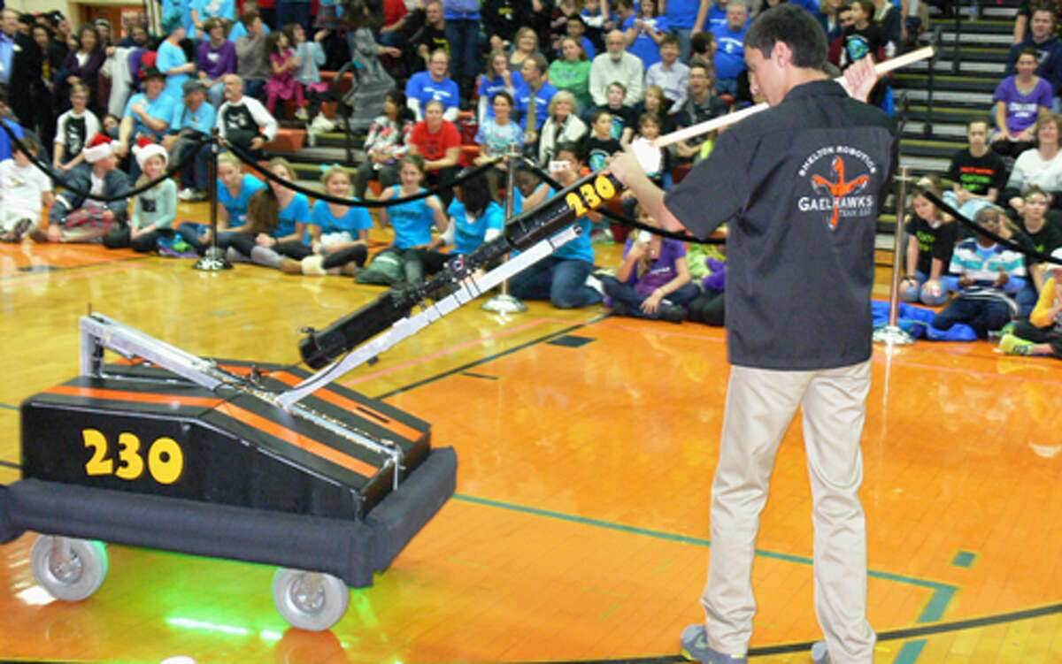 A Shelton High student stuffs a T-shirt into a robot created by the SHS robotics team. The robot would then shoot the T-shirts into the crowd, similar to what occurs at sporting events.