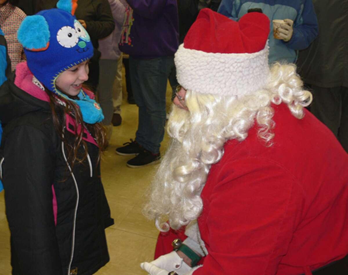 Emma Warner, 7, of Shelton talks to Santa in the firehouse.