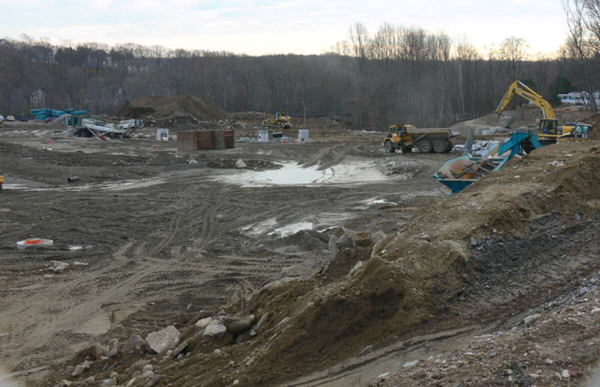 In this photo, on the far right above the yellow piece of construction equipment with a crane, structures from the abutting Fairchild Heights mobile home community can be seen.