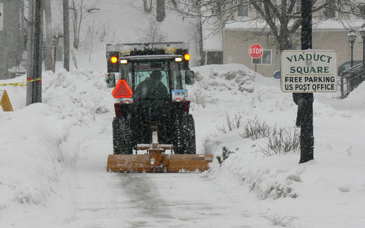 Following a past storm, snow is removed from near the municipal parking lot in front of the post office in downtown Shelton.