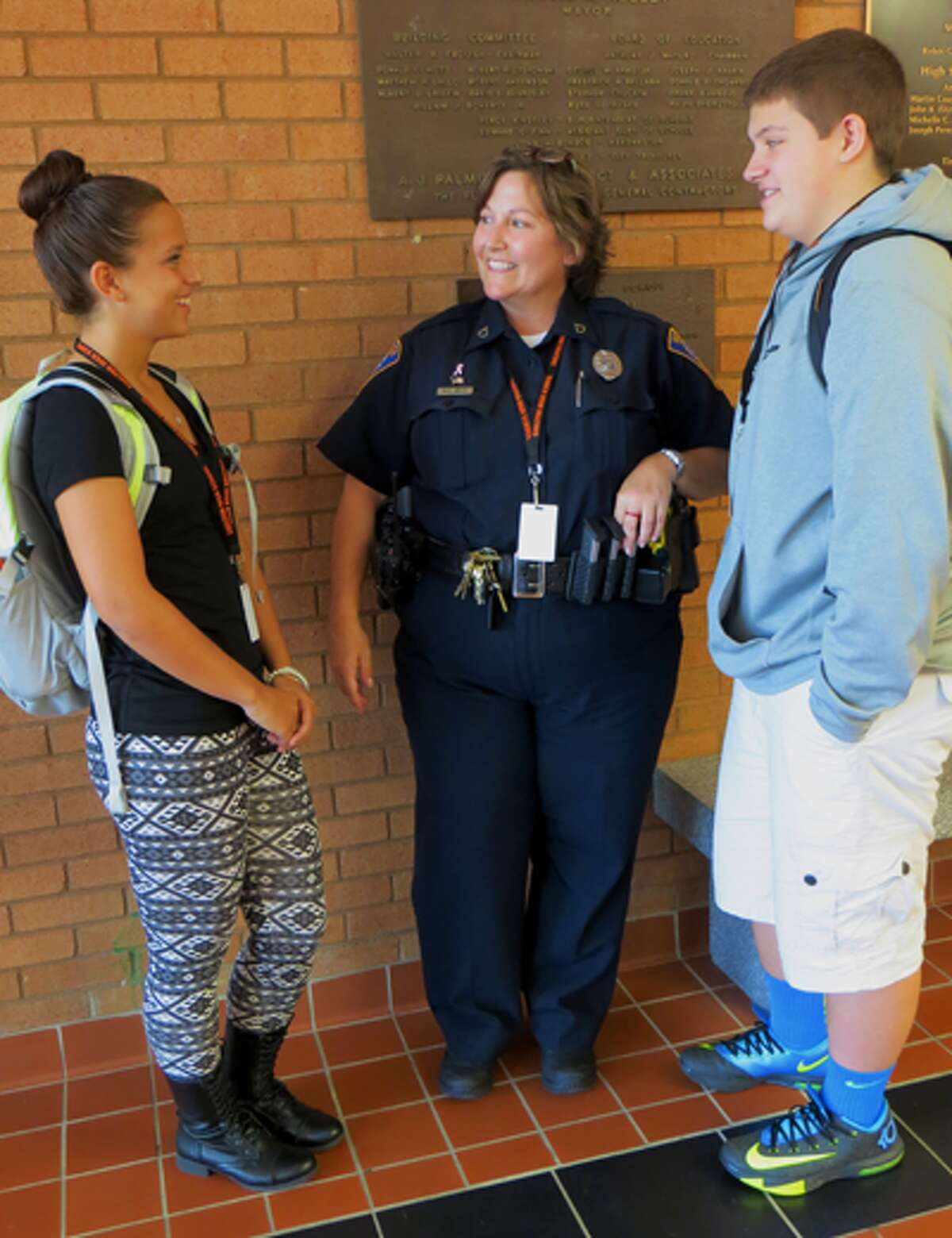 Students Carly Shomski, a senior, and Hunter Garrett, a junior, chat with School Resource Officer Mary Beth White at Shelton High School.