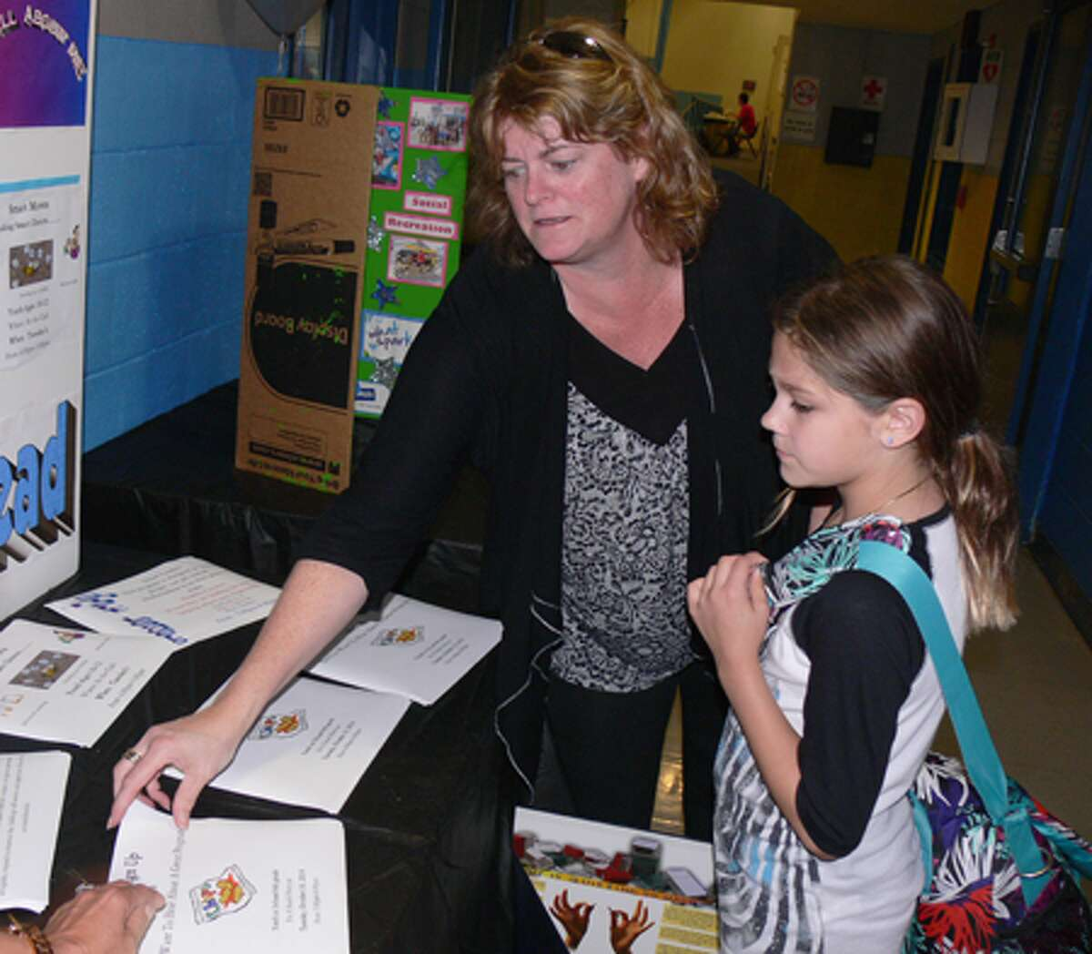 Tricia Santamaria and her daughter Kylin, 8, grab some literature at the Boys & Girls Club open house on Oct. 7 in Shelton.