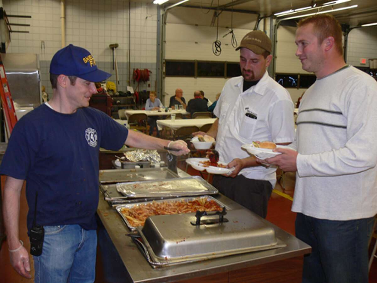 Firefighter Ed Landino dishes out pasta to guests Robert Zimmerman of Shelton, center, and Greg Gross of Stratford at the Pine Rock Park Fire Company's annual ziti dinner.