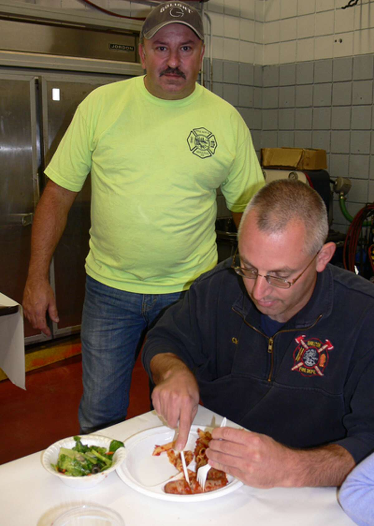 Shelton Fire Chief Fran Jones eats his dinner while Pine Rock Park firefighter Al Pereira looks on.