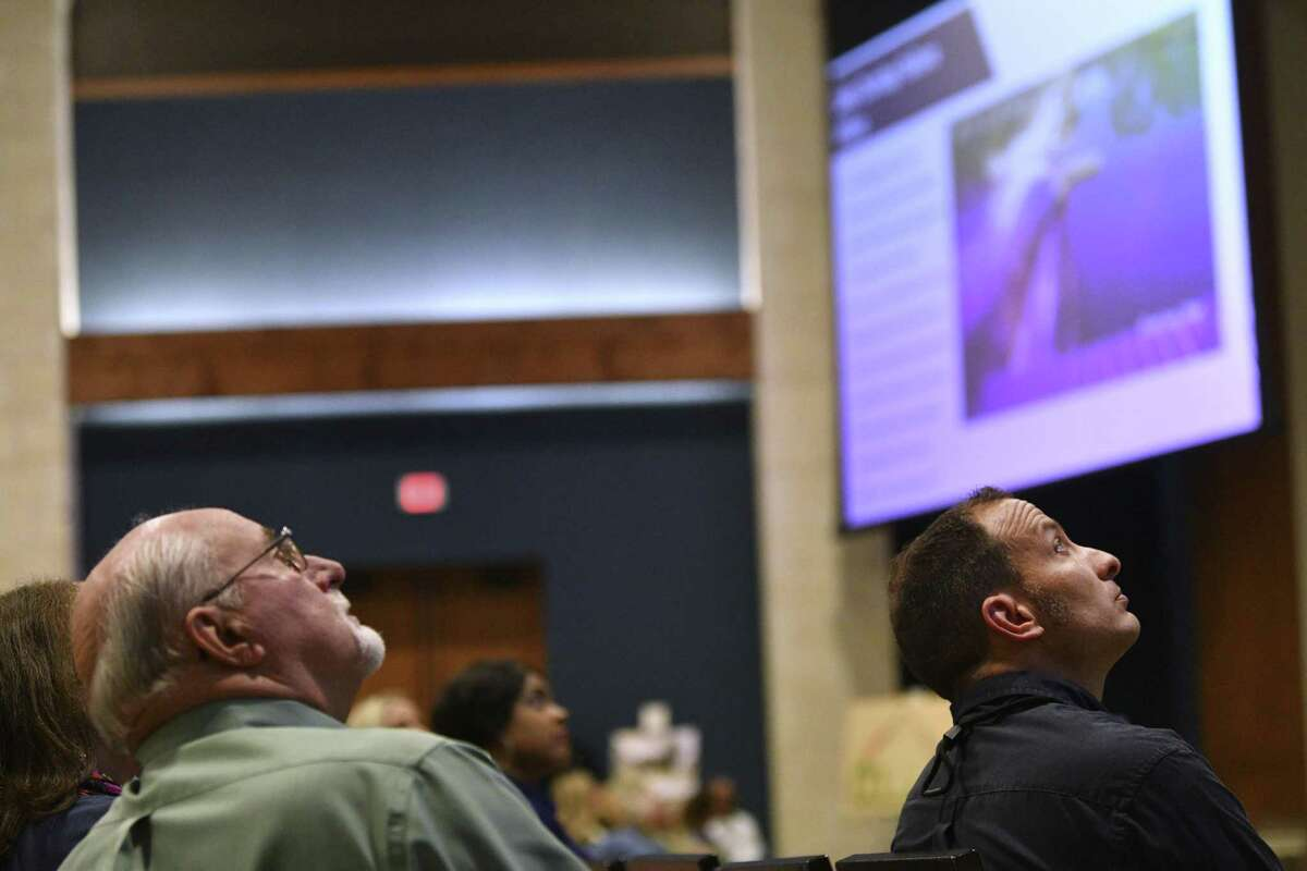People watch a screen showing possible solutions to the damaged dam at Lake Dunlap during a Preserve Lake Dunlap Association meeting to discuss the status of the lake and its failed dam, at the New Braunfels Convention Center in Wednesday, June 5, 2019. The dam that forms Lake Dunlap failed on May 14, draining much of the lake.