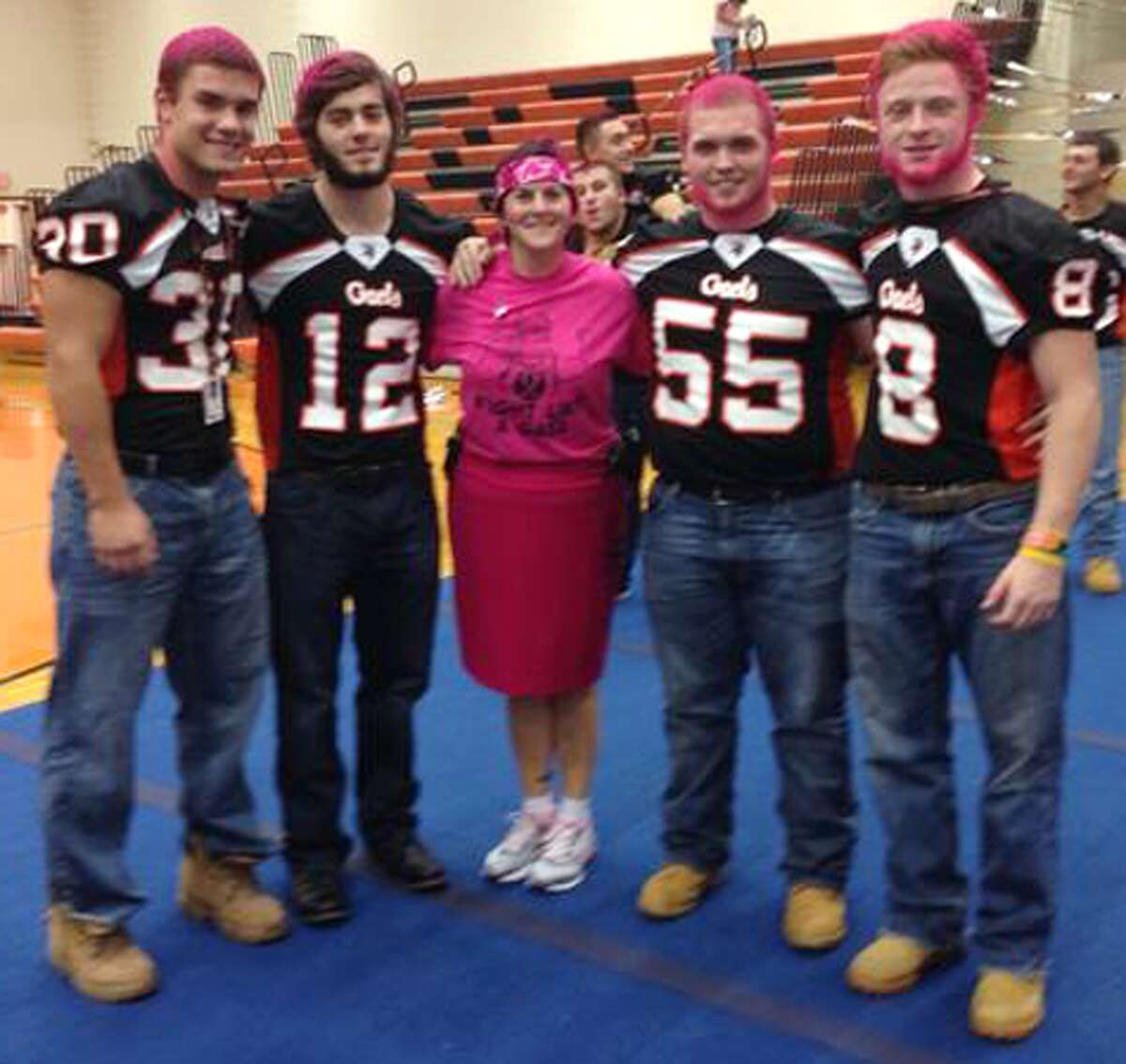 Members of the Gaels football team sport pink haircuts while posing with Shelton High Headmaster Beth Smith.