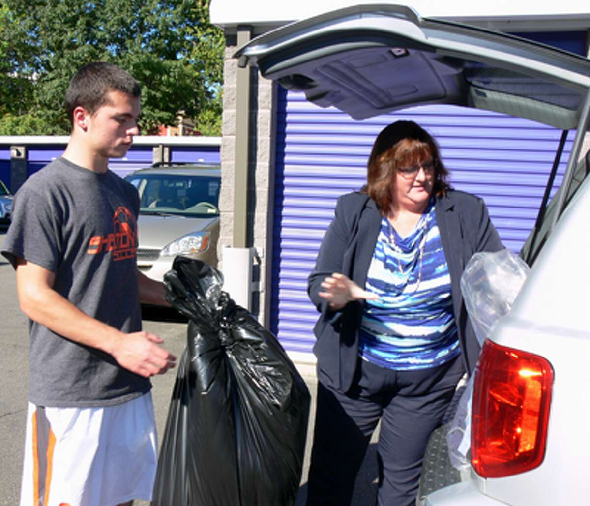 A team member helps out with a last-minute donation before the truck arrives to take all the items away.