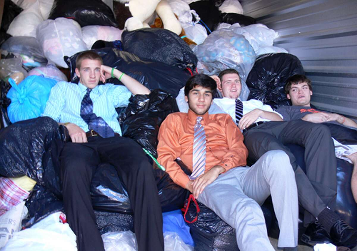 A few SHS soccer team members relax, surrounded by the bagged clothing donations, while waiting for the truck to arrive.