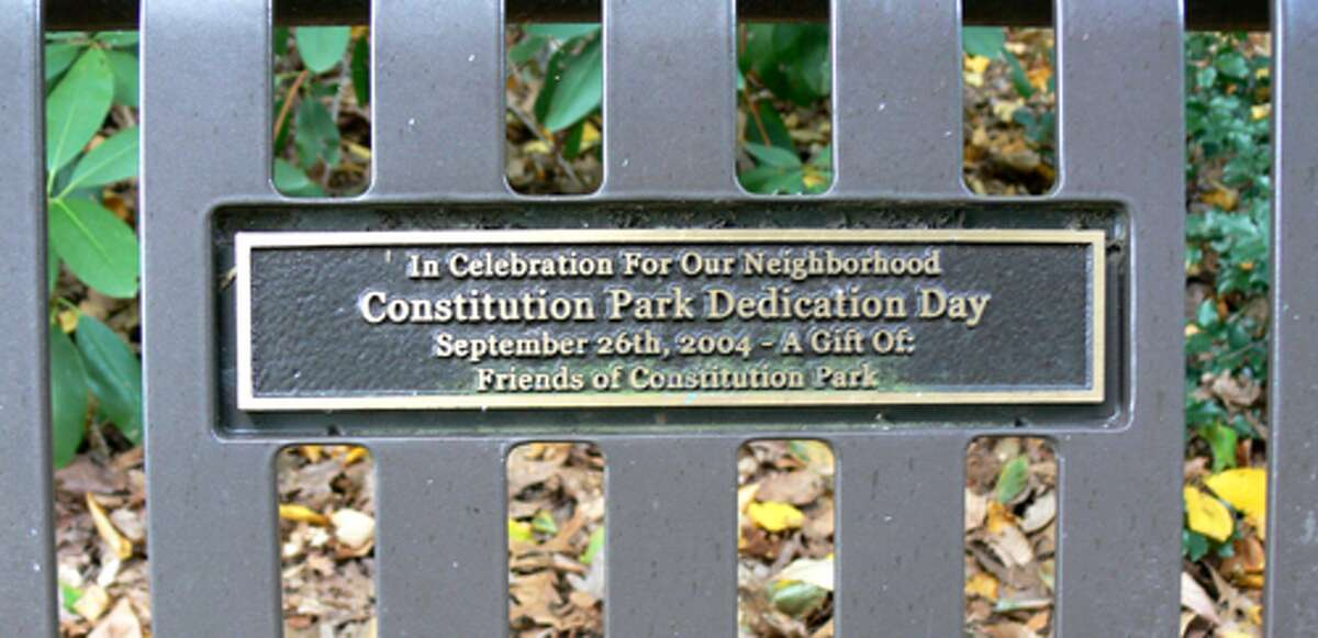 A plaque on one of Constitution Park's five benches notes it is dedicated