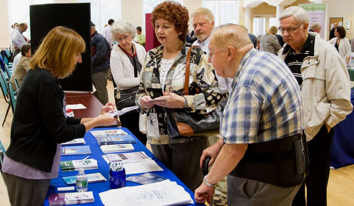 A representative from the Office of the Connecticut Banking Commissioner speaks with seniors during the fair at the Shelton Senior Fair.