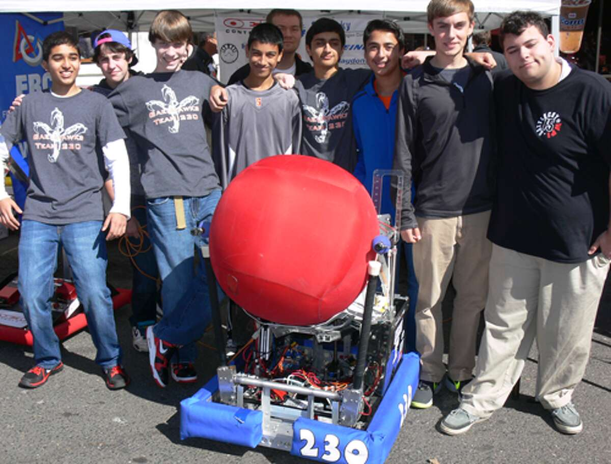 Members of the Shelton High School's Team 230 Gaelhawks - the robotics team - pose with a robot they built.