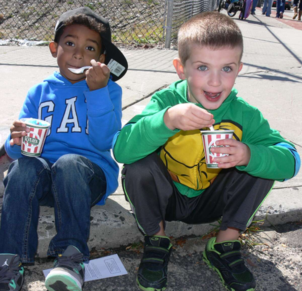 Andre Quick, 4, left, of Derby and A.J. Hatfield, 5, of Shelton eat Italian ice while relaxing on the sidewalk at Shelton Day. The two are friends from pre-school.