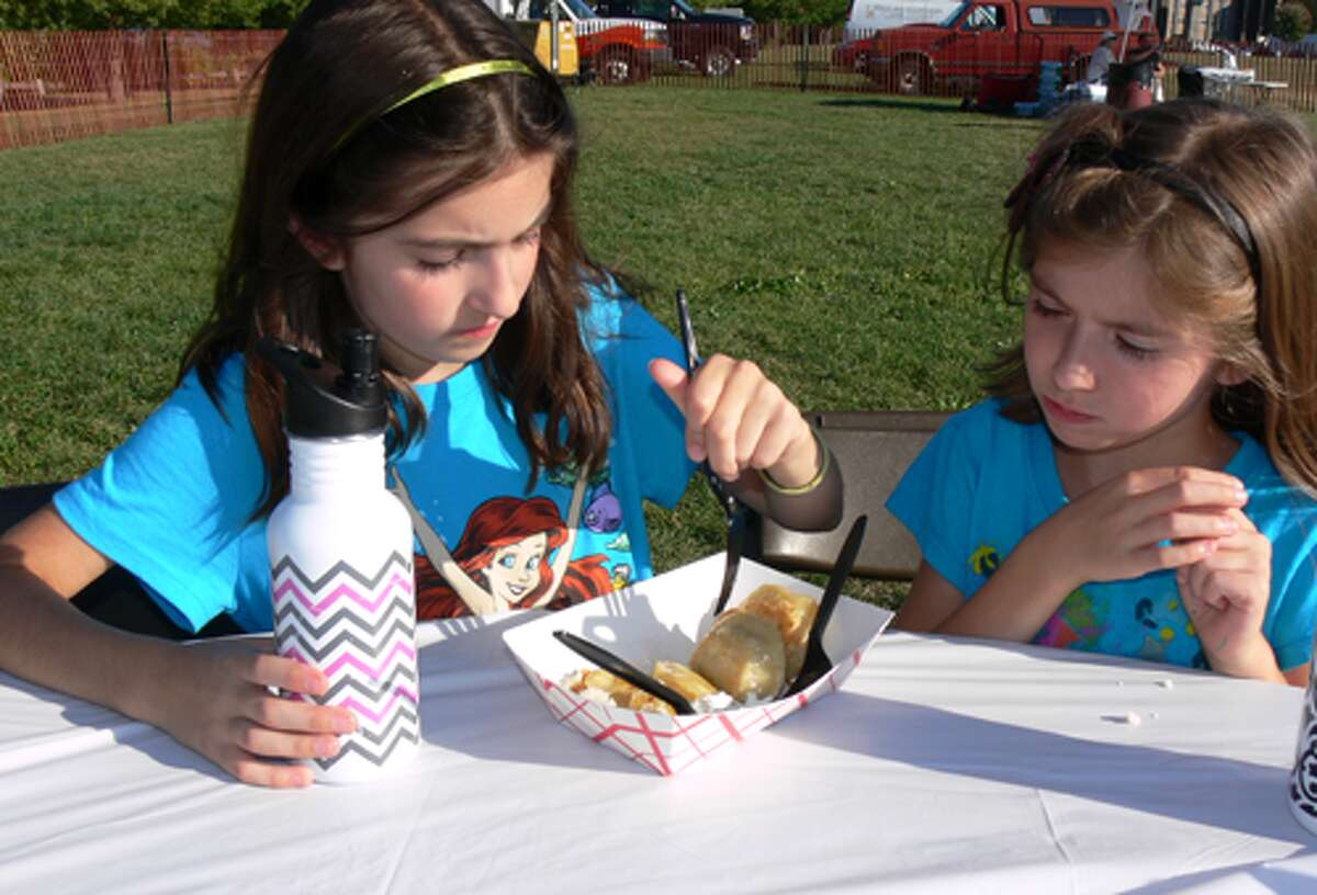 From left, sisters Amy Prancuk, 10, and Zoe, 7, of Shelton try the perogies at the event.