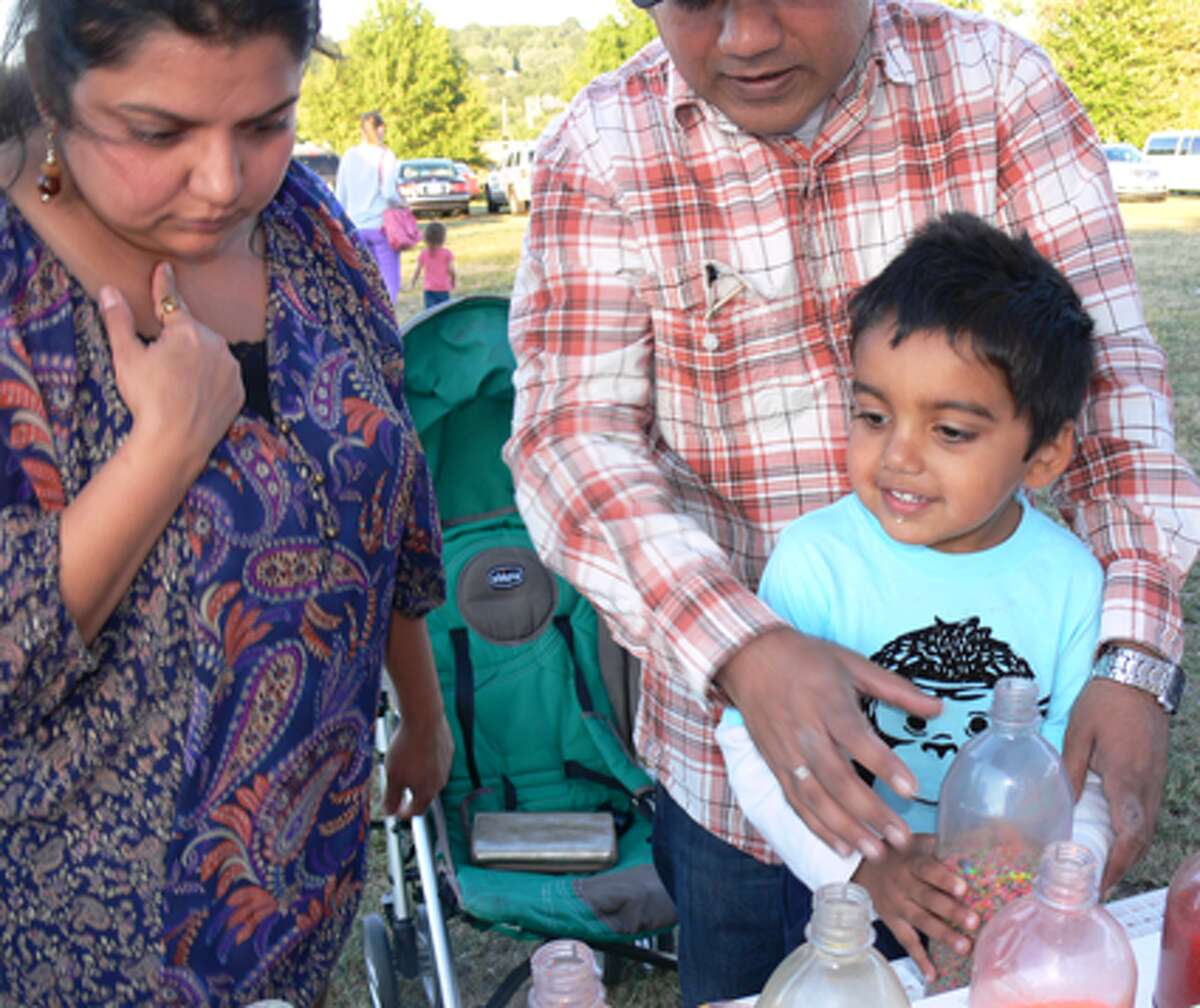 Raunak Saini, 3, of Shelton makes a candle with sand art while joined by mother Nidhi and father Dev.