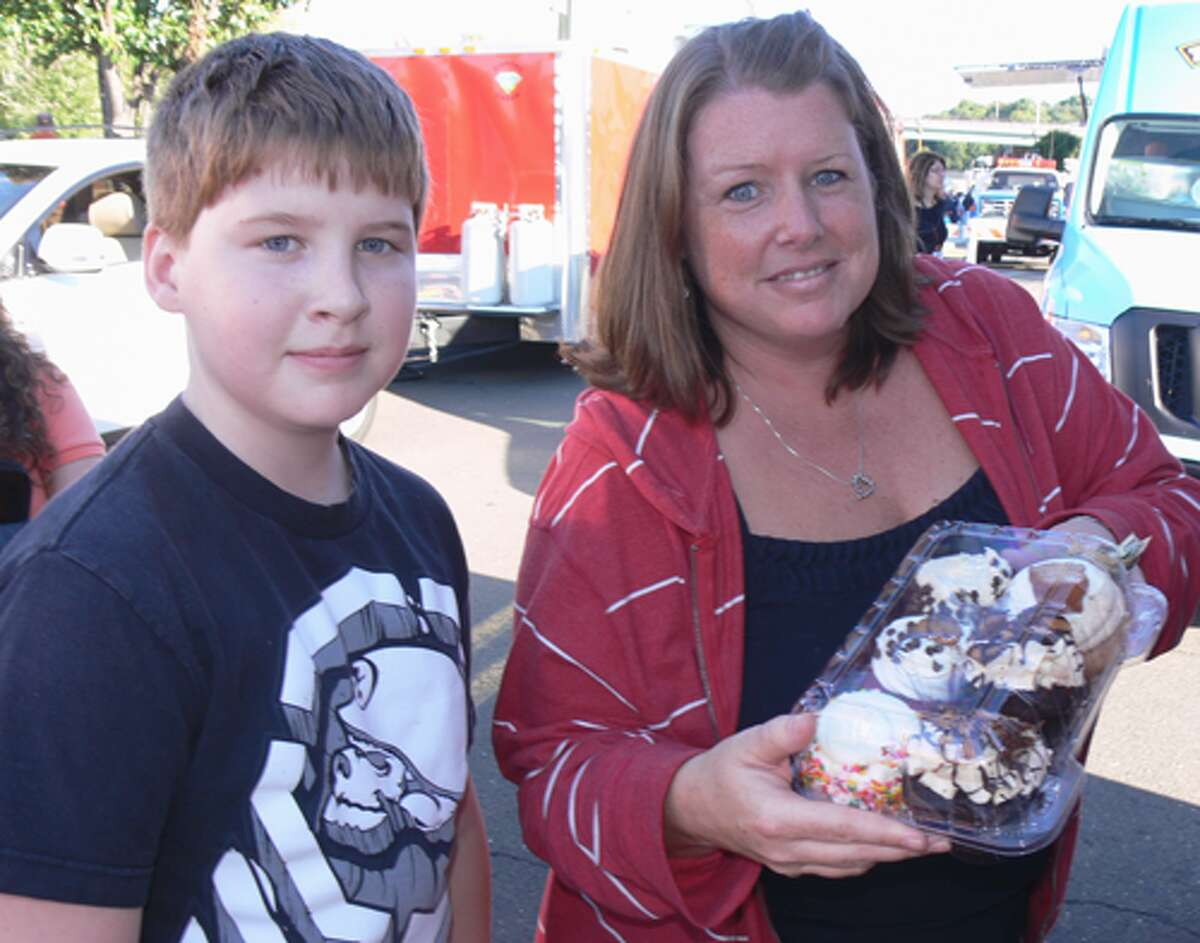 Tracy Platt of Shelton, with 13-year-old son Nate, buy a half dozen cupcakes to take home from the Hardcore Sweet Cupcake Truck.