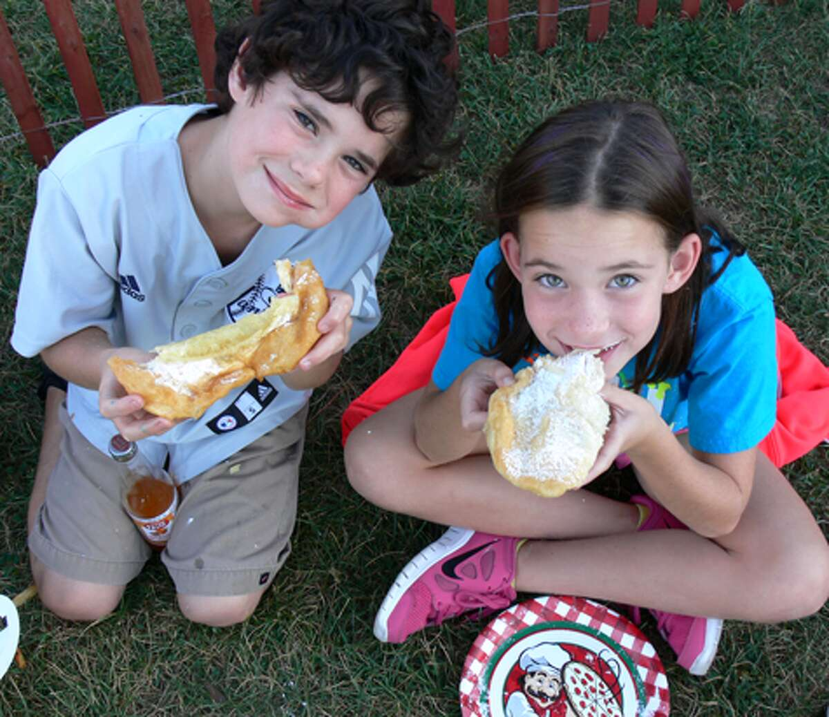 Mac and Ireland Starziski, 10-year-old twins from Naugatuck, are all smiles as they devour fried pizza dough. They were with siblings Skyla, 10, and Ty, 6, as well as mom Amy.