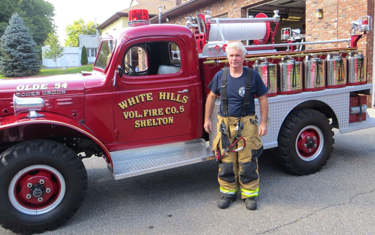 Volunteer Shelton firefighter Tony Martinka stands near the White Hills Company antique fire truck.