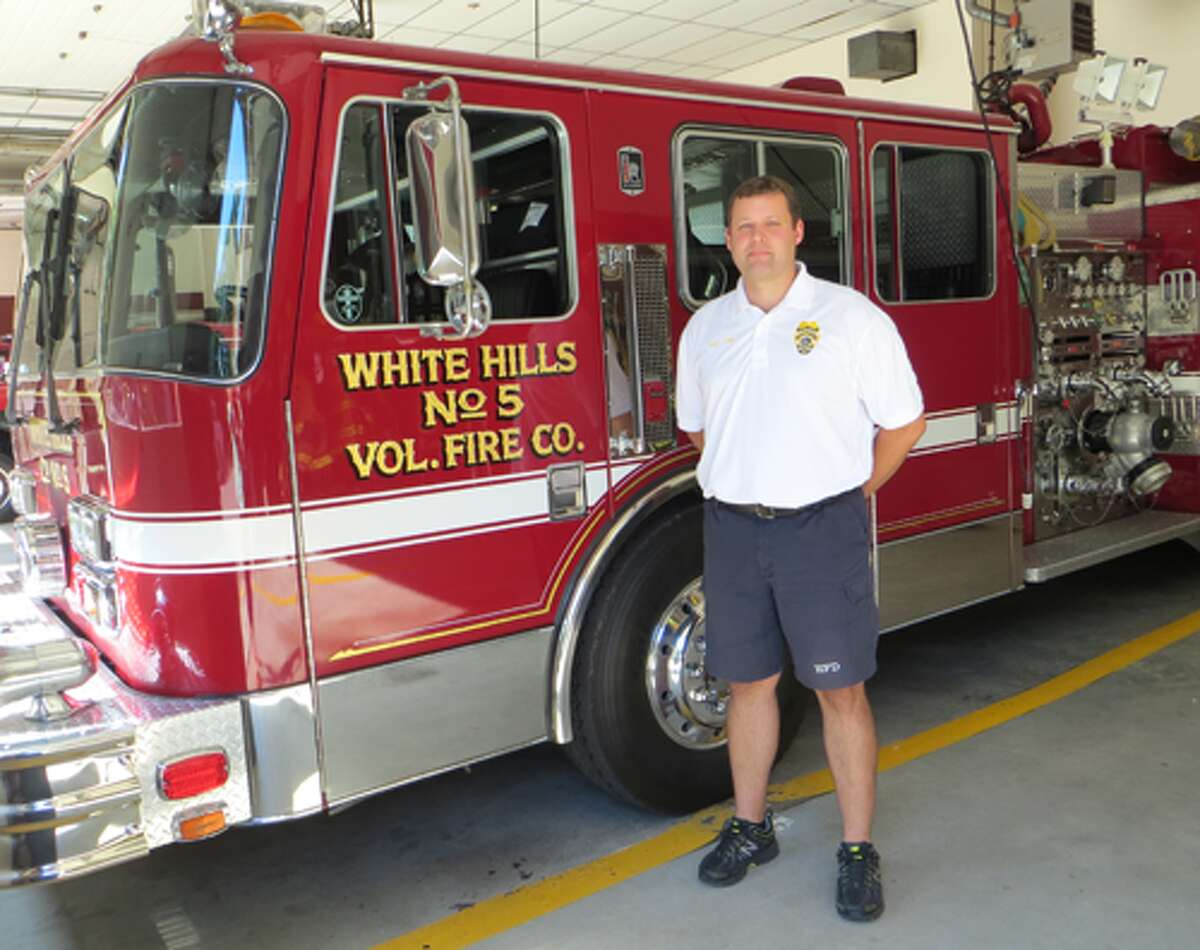Asst. Chief Daryl Osiecki stands in one of the bays at the White Hills firehouse.