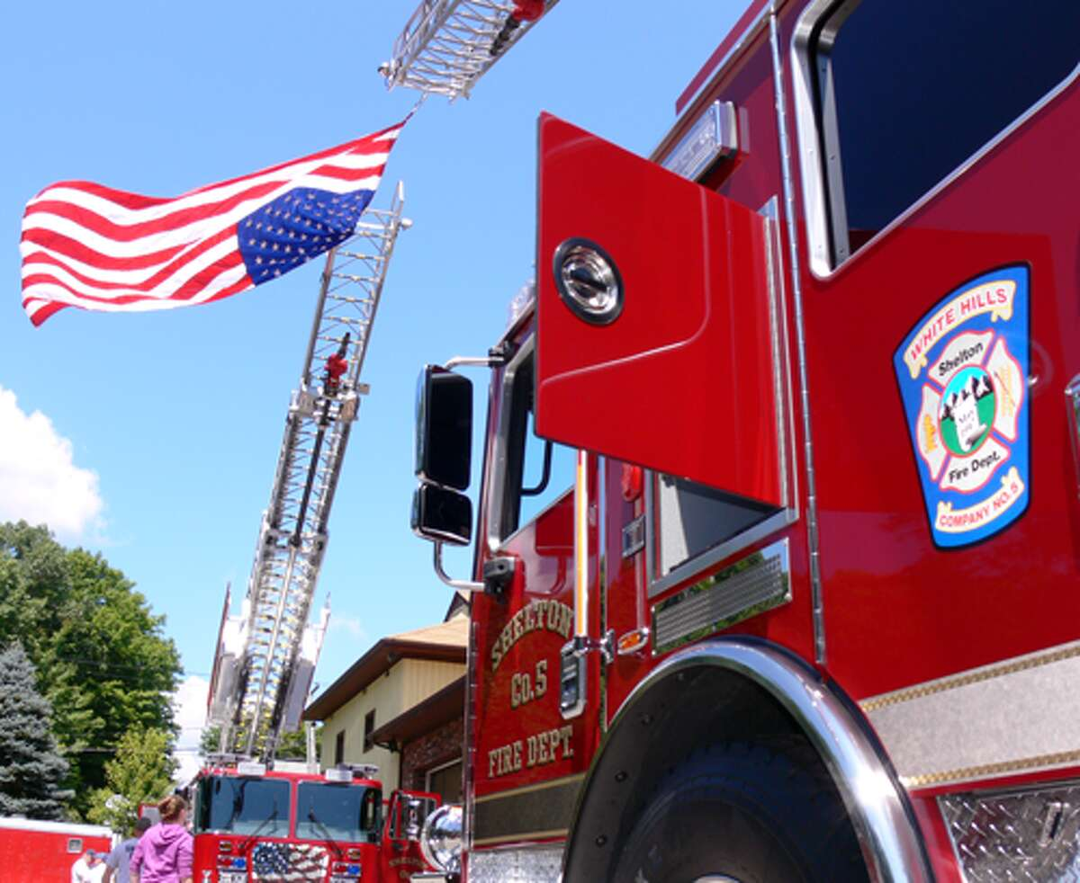 The two new fire trucks on display, with an American flag hanging between the two ladders.