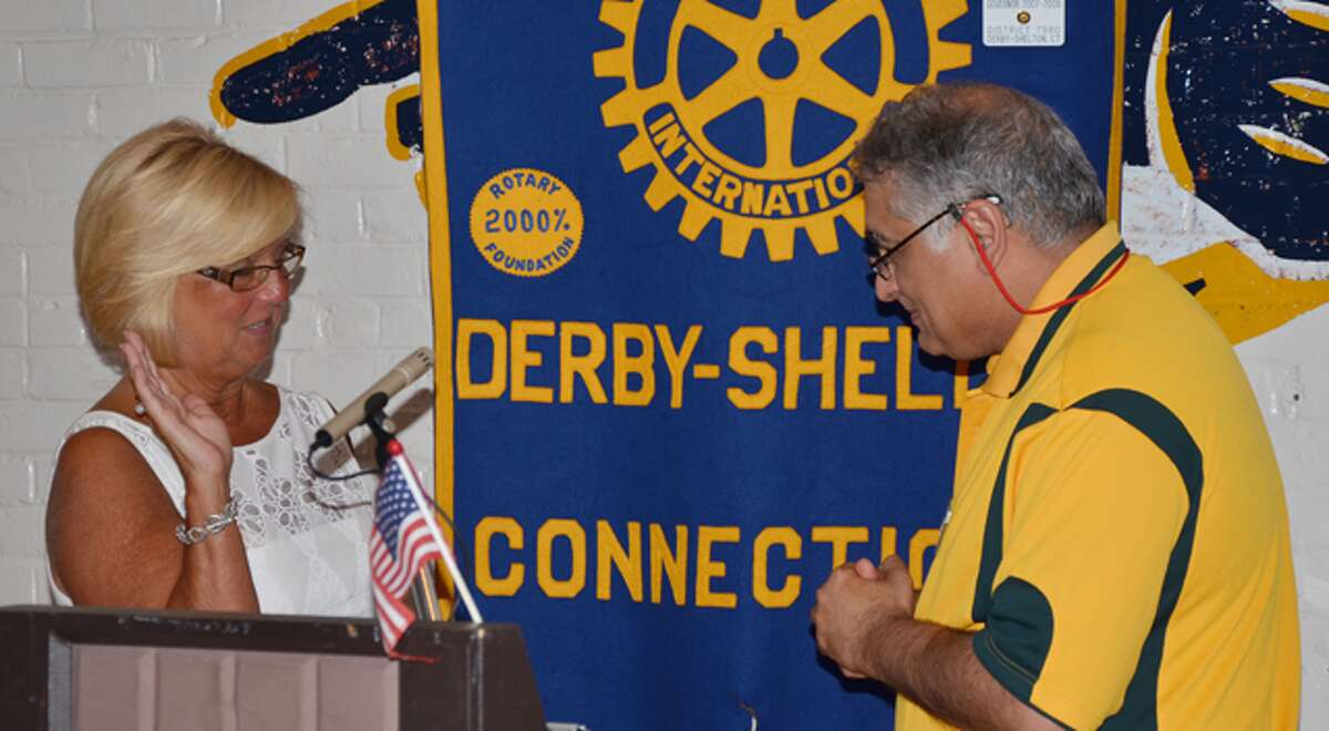 Cindy Rinaldi of Shelton, left, is sworn in as 2014-15 Derby-Shelton Rotary Club president by Mukund Nori, a Rotary International district governor.