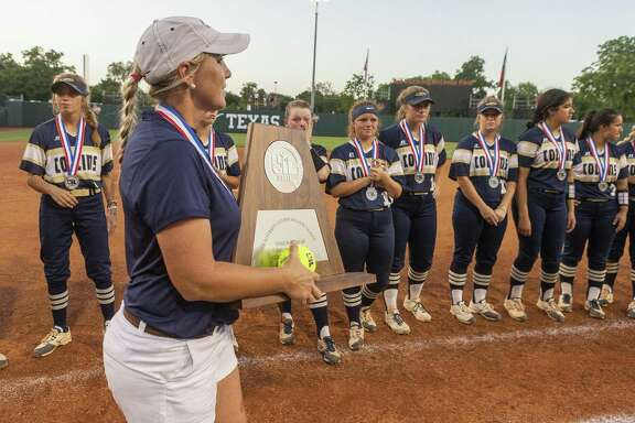 Klein Collins head coach Audra Troutman holds the runner-up trophy as the team stands with their silver medals after falling to Katy 8-2 during the UIL Class 6A state softball championship in Austin, Saturday, June 1, 2019. (Stephen Spillman / for Houston Chronicle)