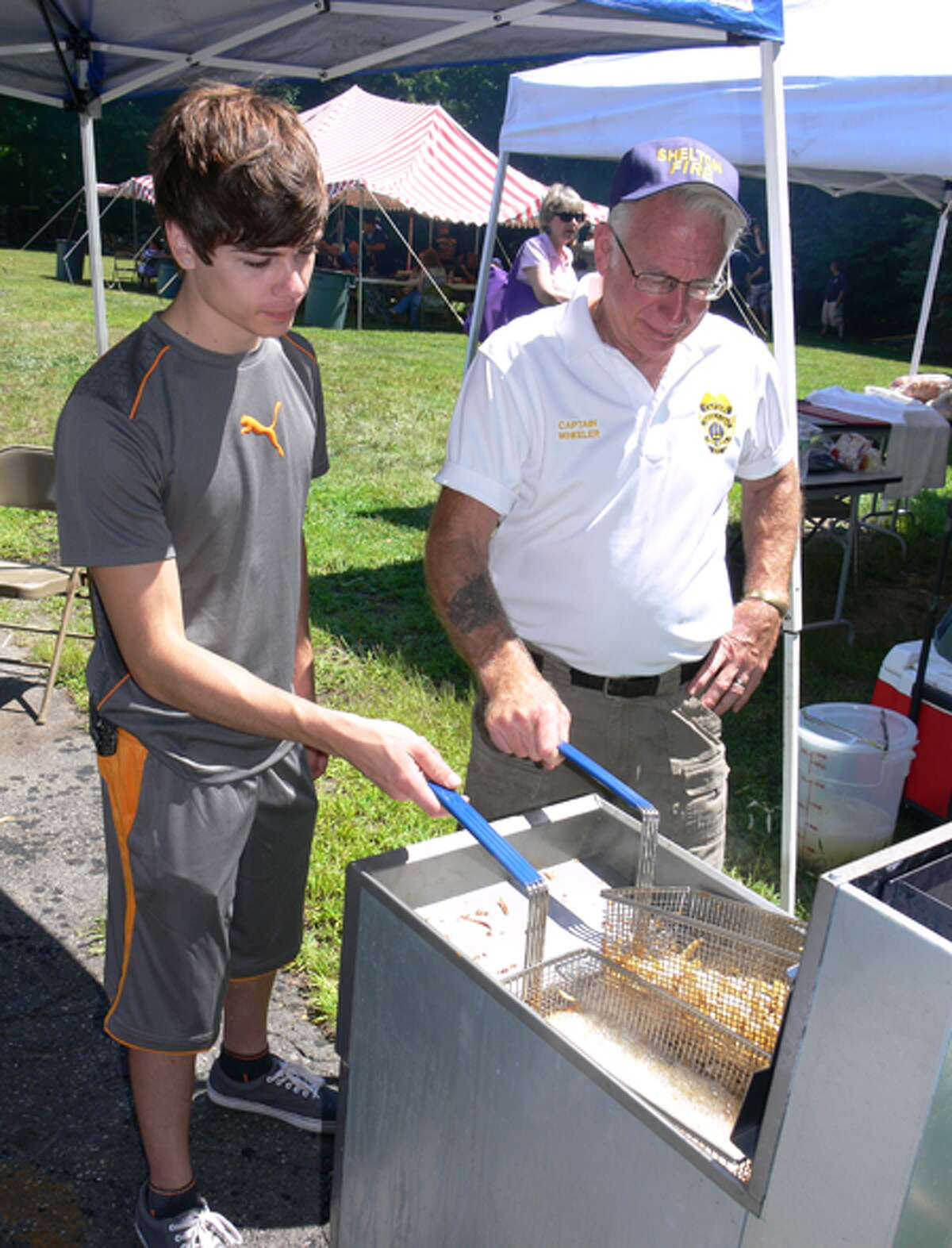 Making French fries during the event are White Hills Fire company members, from left, Andrew Kopac, 20, and Capt. Fran Wheeler.
