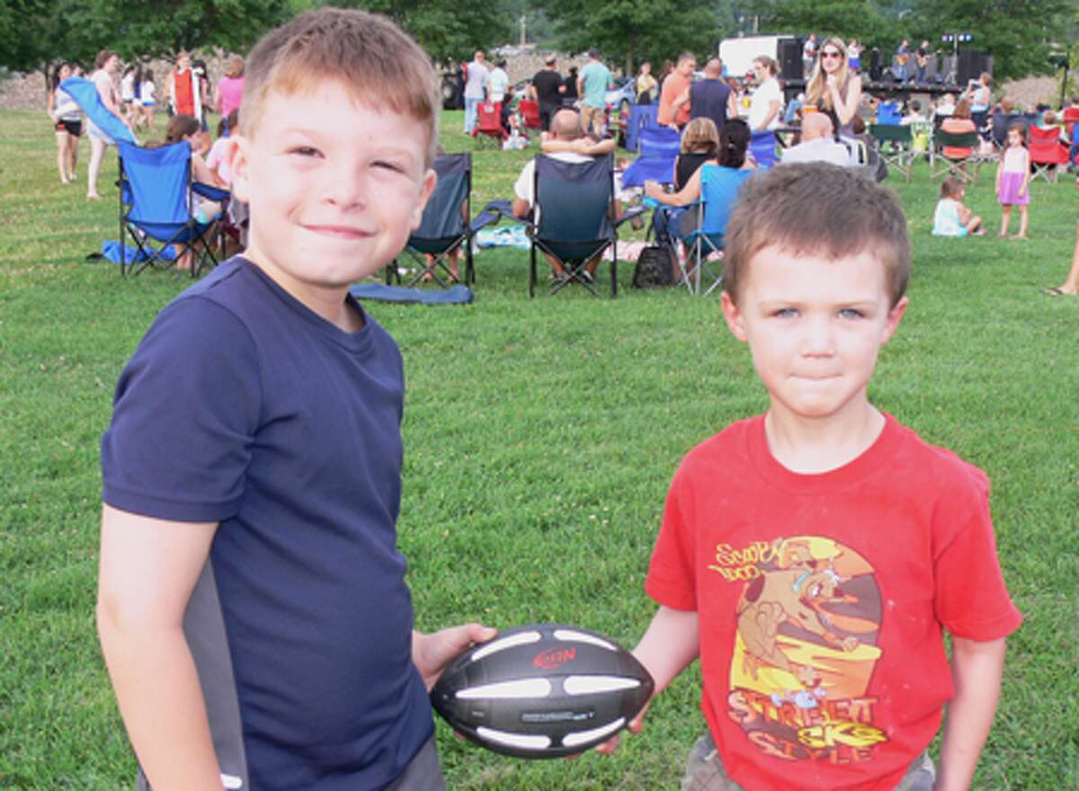 Logan Page, left, and friend Brendan take a break from throwing a football.