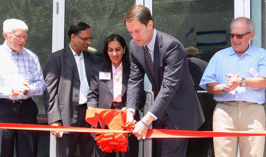 U.S. Rep. Jim Himes cuts the ribbon at the new NanoViricides facility in Shelton while joined by company officials, including President and Chairman Anil R. Diwan, Interim Chief Financial Officer Meeta Vyas and Chief Executive Officer Eugene Seymour.