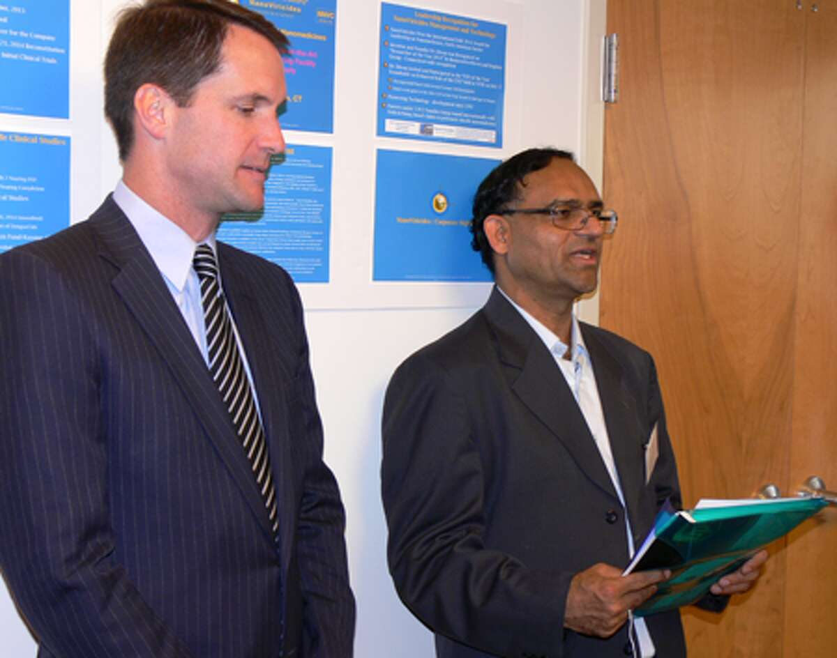 Congressman Jim Himes, left, listens as NanoViricides Inc. founder Anil R. Diwan speaks at the opening of the company's Shelton facility.