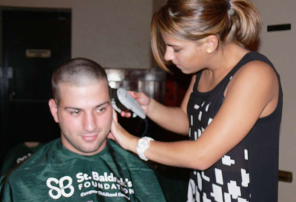 Tina Tassitano finishes cutting the hair of her brother, Joey.