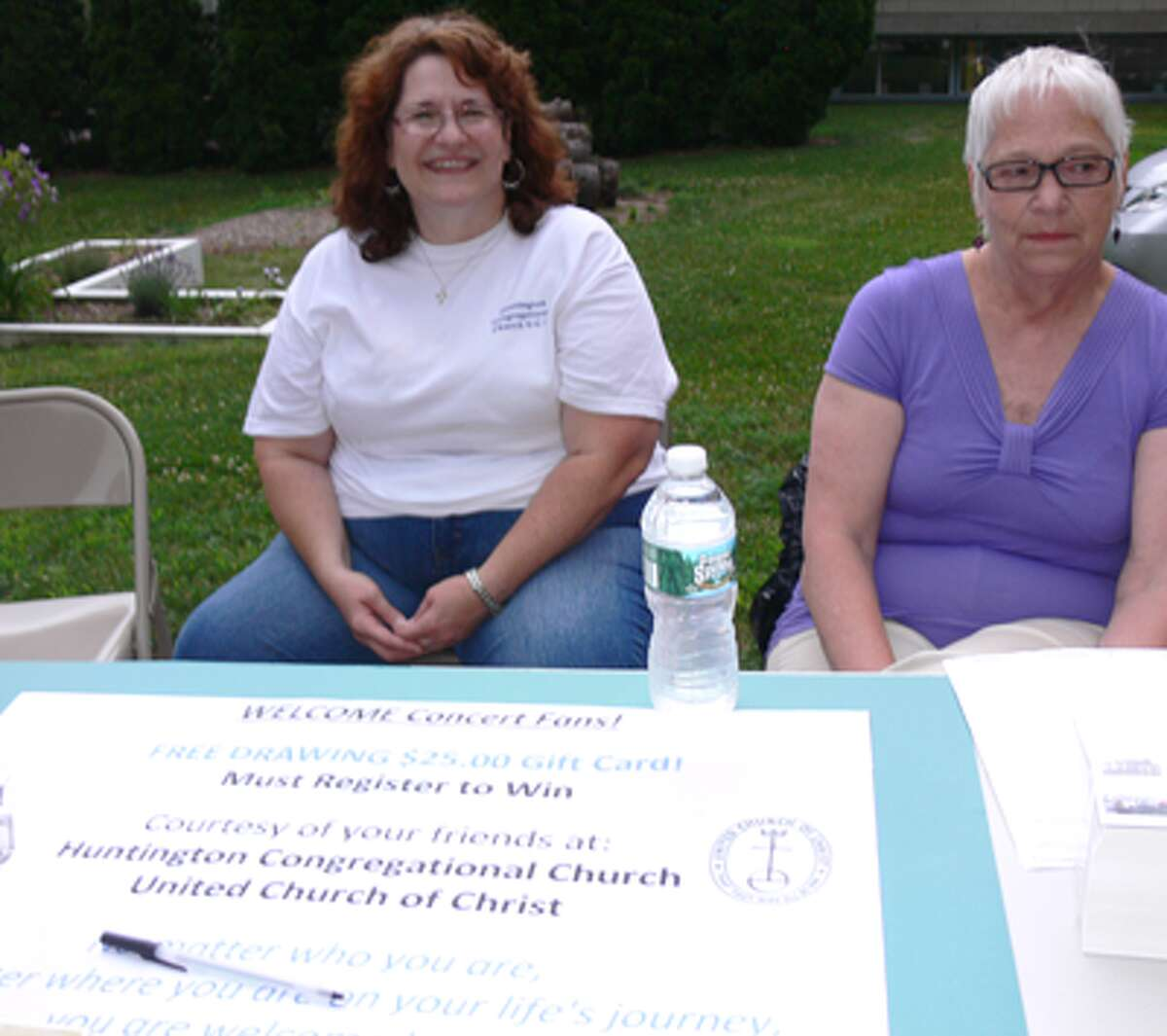 The Rev. Lucille Fritz of Huntington Congregational Church, left, and church member Gail Schoennagel staff the raffle and bottled water table in the church's parking lot during a concert.