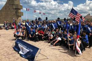 The Albany Marching Falcons, the city school district's marching band, participate on Thursday, June 6, 2019, in commemorative exercises on the beach in Normandy, France, marking the 75th anniversary of D-Day.