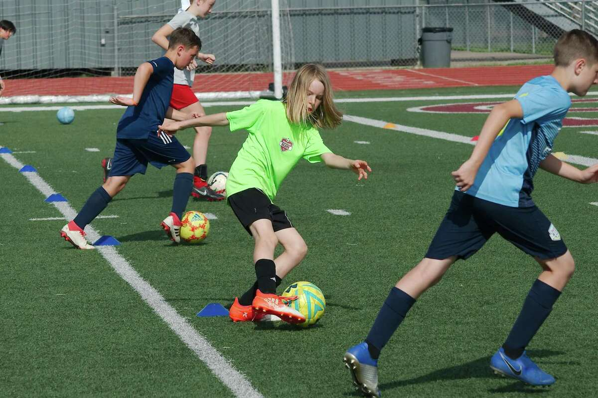 Taylor Schaefer (center) participates in a dribbling drill at the Pearland summer soccer camp at The Rig.