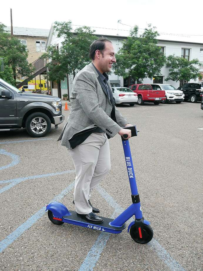County Treasurer Raul Reyes rides a Blue Duck Scooter after a city press conference last week. Photo: Cuate Santos / LMT File / Laredo Morning Times