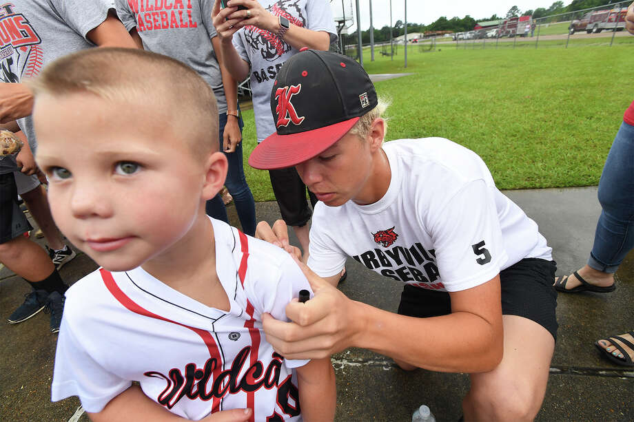 The WIldcat's Logan Webb signs Thursday the back of Jett Peel's, 5, shirt during the Kirbyville baseball team's send off to play in this year's state tournament. The team was fed breakfast then cheered on by a crowd as their bus pulled away to Roundrock. The Wildcats will play Wall at 9 a.m. Friday. Photo taken Thursday, 6/6/19 Photo: Guiseppe Barranco/The Enterprise / Guiseppe Barranco ?