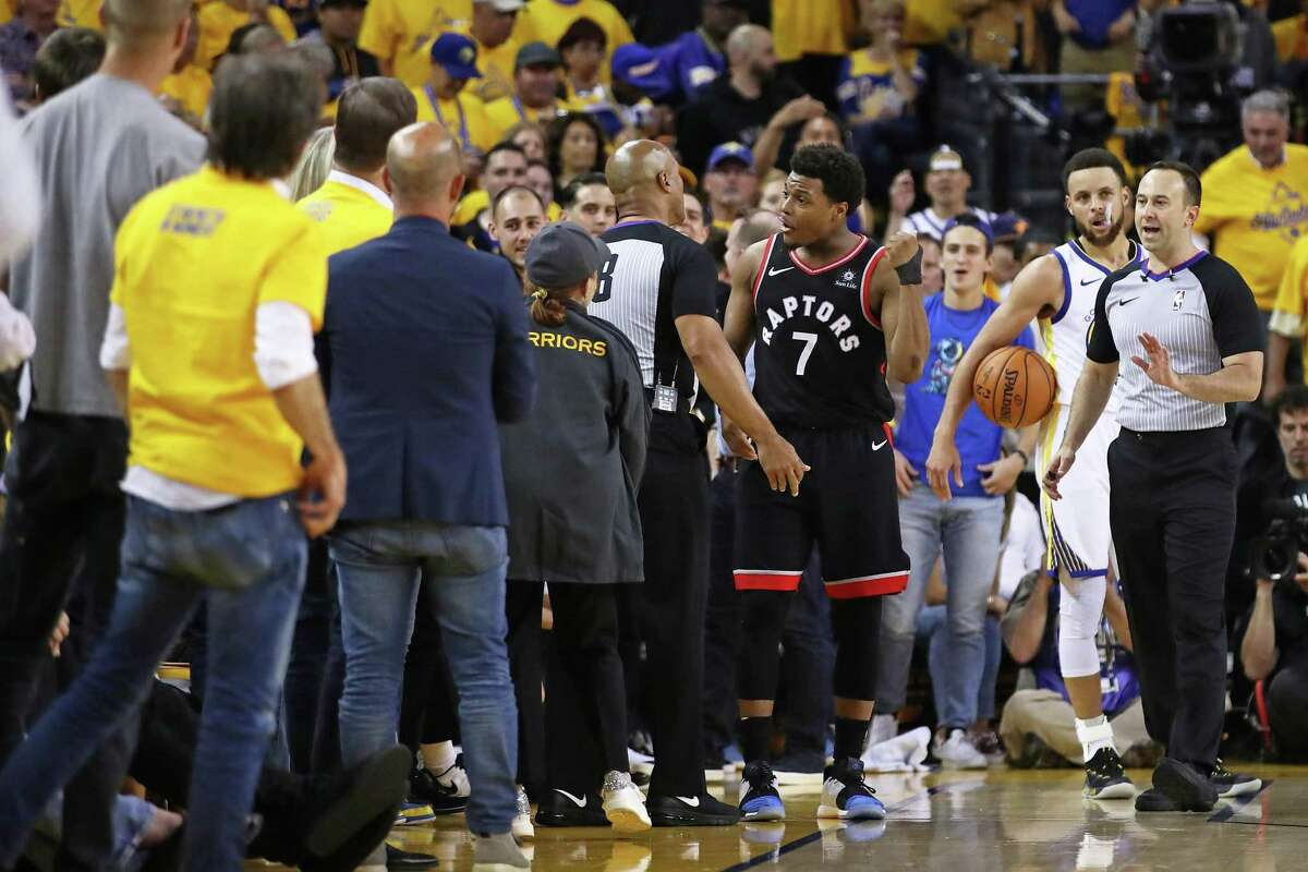 Kyle Lowry of the Toronto Raptors complains to referee Marc Davis after Warriors minority owner Mark Stevens shoved him when Lowry landed in a row of fans while going for a loose ball during Game 3 of the NBA Finals at Oracle Arena.