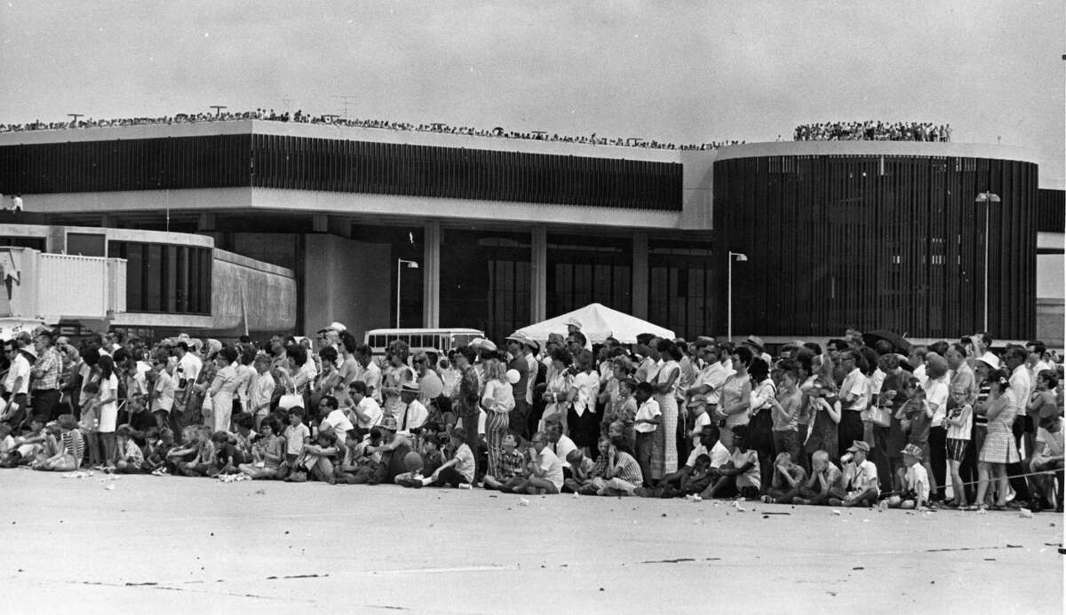 Crowds line the roof of terminal for Intercontinental Airport open house, June 1, 1969. Others sit and stand along taxing area to see air show.