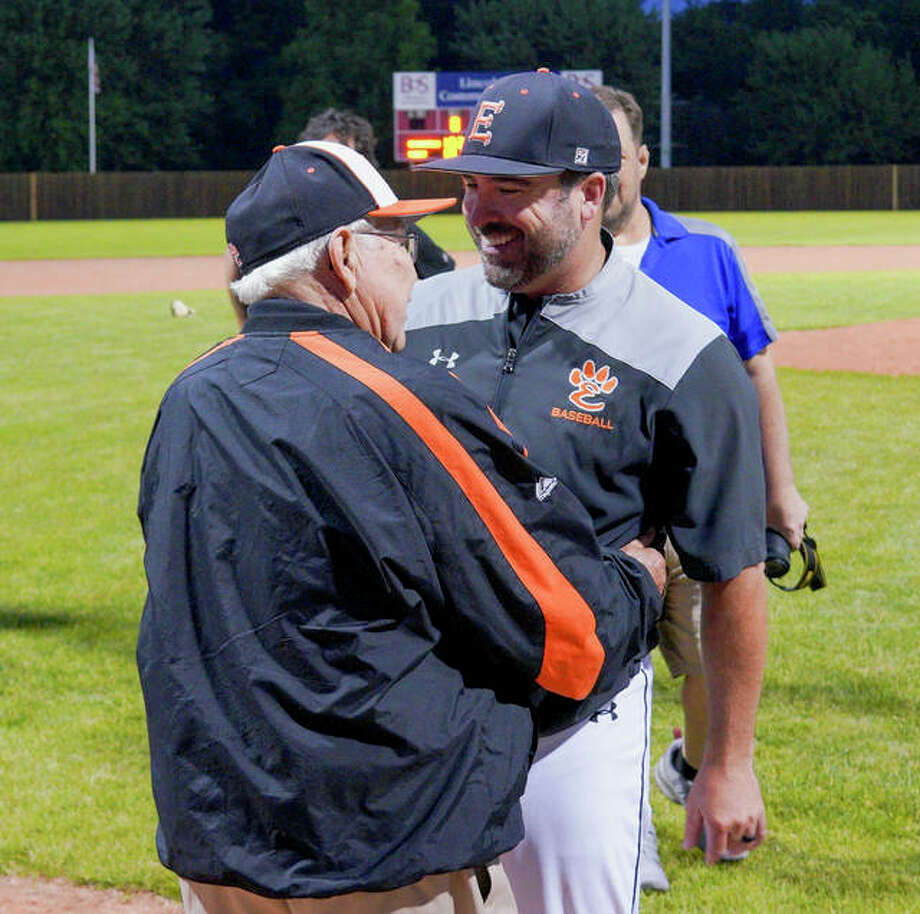 Edwardsville coach Tim Funkhouser, right, is congratulated by his dad, Bill, after the Tigers clinched a trip to the Class 4A state tournament with a 6-5 win over Chicago Marist on Monday.