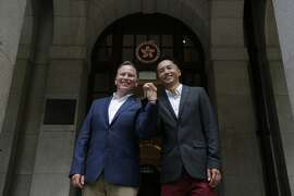 Angus Leung Chun-kwong, a senior immigration officer, right, and Scott Adams, a same-sex couple who married in New Zealand five years ago, pose for photographers outside the Court of Final Appeal in Hong Kong, Thursday, June 6, 2019. Hong Kong's Court of Final Appeal said Thursday the government cannot deny spousal employment benefits to same-sex couples, in a ruling hailed as a major step forward for same-sex equality in the semi-autonomous Chinese territory. (AP Photo/Kin Cheung)
