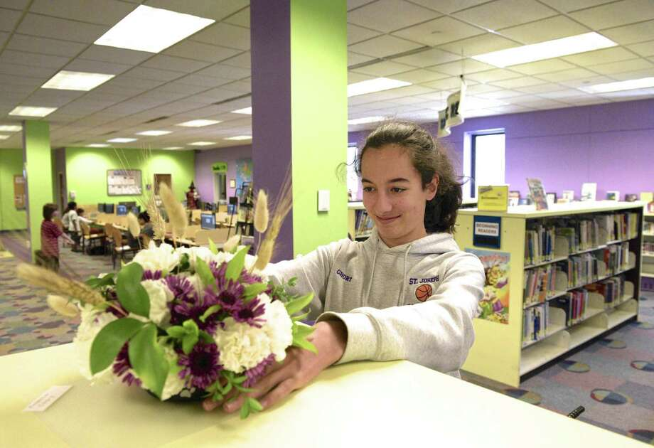 """Rebecca Chory, 12, of Danbury, places a floral arrangement on top of a book case in the junior section of the Danbury Library Tuesday afternoon. Danbury Garden Club members as well as Junior Garden Club members created floral designs for """"Books in Bloom"""" to celebrate the library's 150 years of service to the community. June 4, 2019, in Danbury, Conn. Photo: H John Voorhees III / Hearst Connecticut Media / The News-Times"""