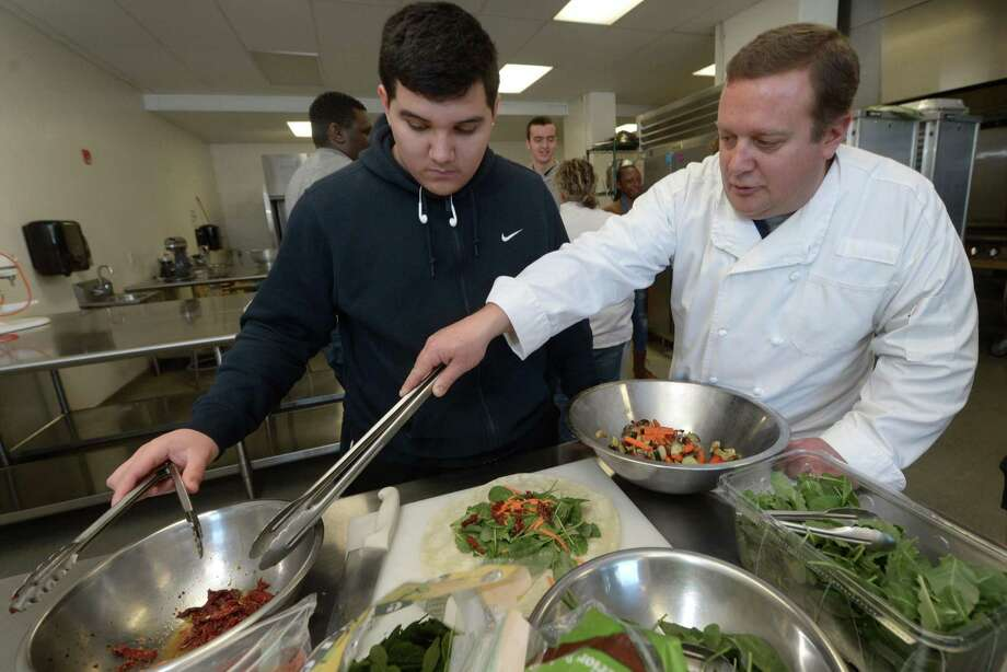 Senior Jake Lovo gets help from culinary teacher Ted White as they prepare food for faculty members during the Norwalk High School culinary program Wednesday, January 10, 2018, at the school in Norwalk, Conn. The culinary program may become a certificate program through a partnership with Norwalk Community College. Photo: Erik Trautmann / Hearst Connecticut Media / Norwalk Hour