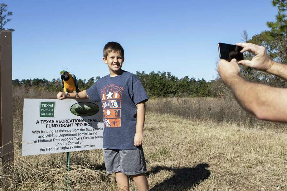 Joshua Hamann, right, stands with Tiki Macaw at the westernmost trailhead of the 13-mile Spring Creek Nature Trail as Robert Hamann takes a photo before the opening ceremony for the trailhead Thurssday, Dec. 20, 2018 at Creekside Park West in The Woodlands. Photo: Cody Bahn, Houston Chronicle / Staff Photographer / © 2018 Houston Chronicle