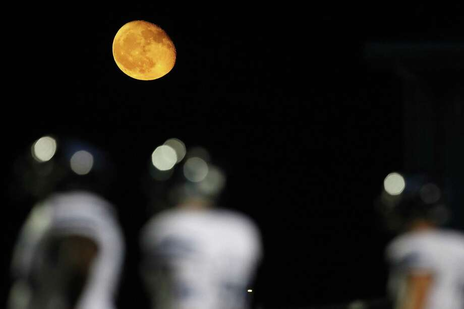 The moon, shown shining behind Friendswood High School football players in 2017, and NASA's lunar missions have played a prominent role in Friendswood's development. Photo: Brett Coomer, Staff / Houston Chronicle / © 2017 Houston Chronicle