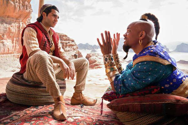 """Mena Massoud as Aladdin, left, and Will Smith as Genie in Disney's live-action adaptation of the 1992 animated classic """"Aladdin."""""""
