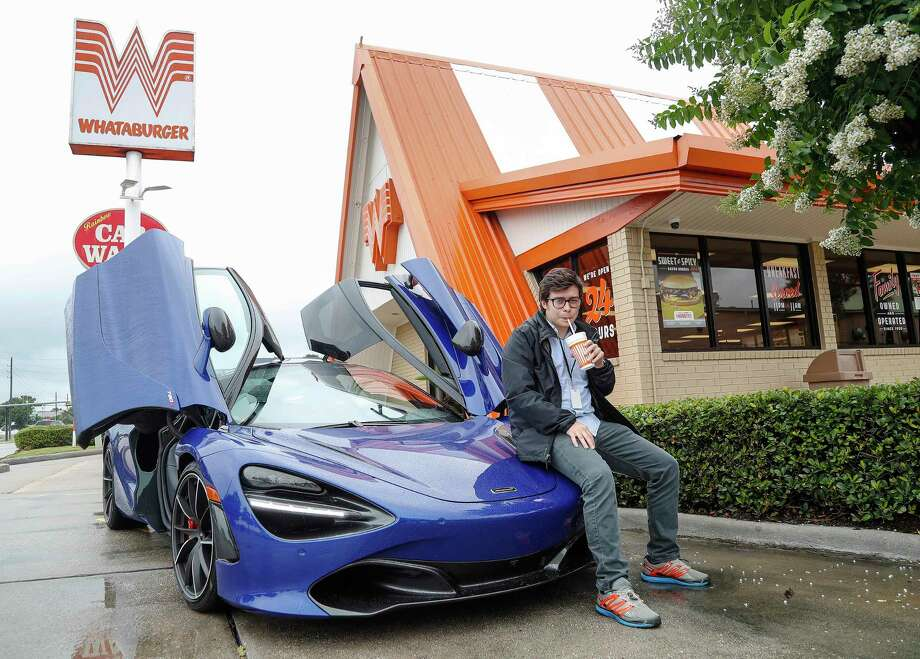Houston Chronicle reporter Julian Gill drinks a soda as he test drove a McLaren 720S Coupe in the driveway of a Whataburger, Wednesday, June 5, 2019. Photo: Karen Warren, Staff Photographer / © 2019 Houston Chronicle