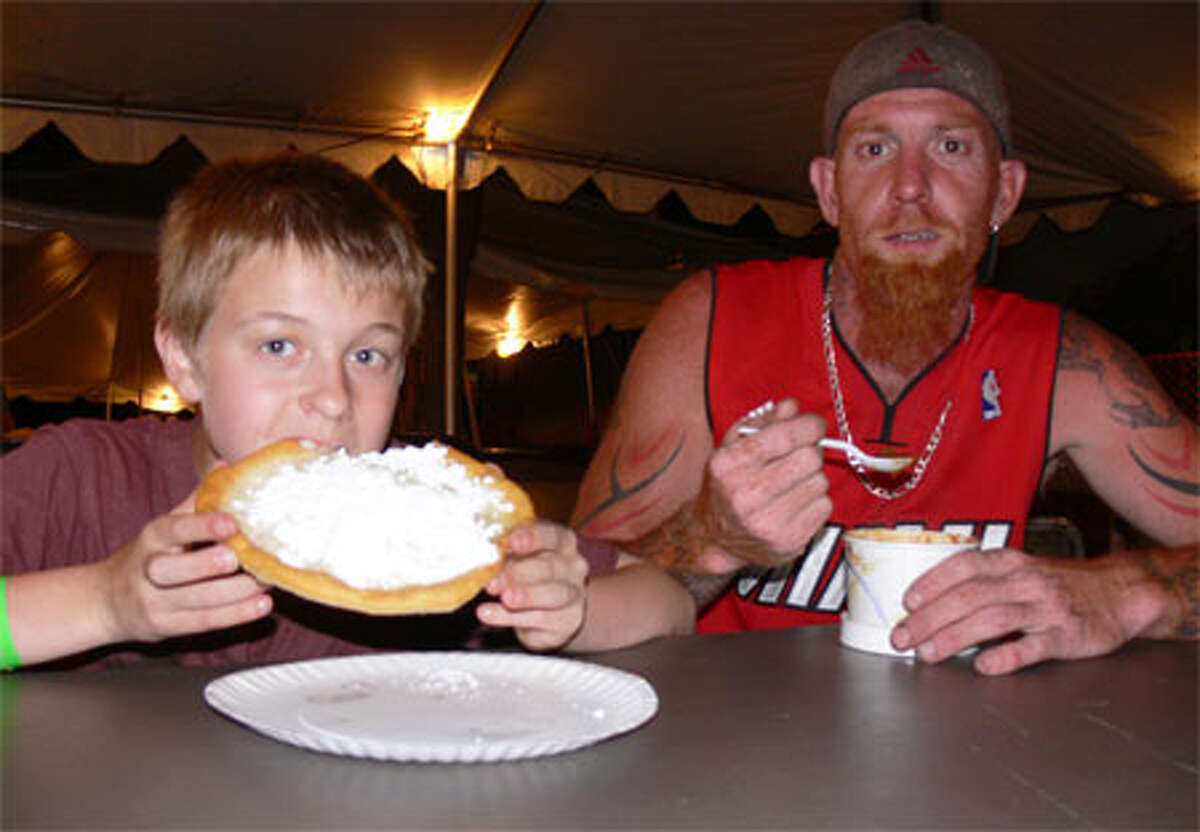 Fred Davino, 10, of Shelton bites into his fried dough with powdered sugar during the 2013 St. Joseph Carnival while joined by his father, Carl, who is enjoying a bowl of chili.