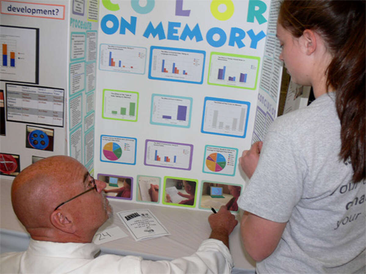 Bob VanEgghen of PerkinElmer talks to student Allison Nielson about her project at the Shelton Intermediate School Science Fair. VanEgghen was a judge in the fair.